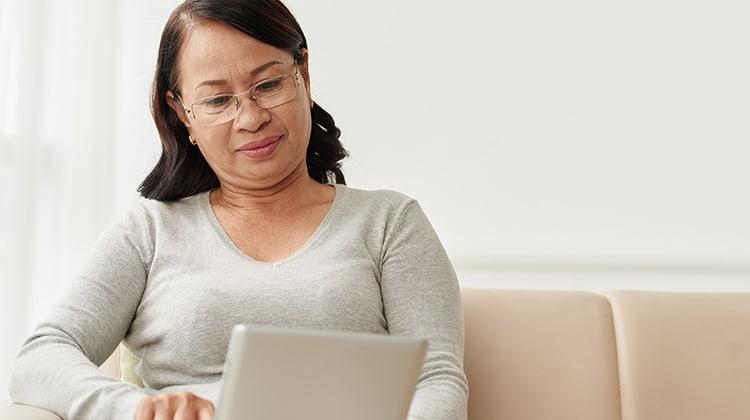 Mature Vietnamese woman enjoying book on her tablet computer