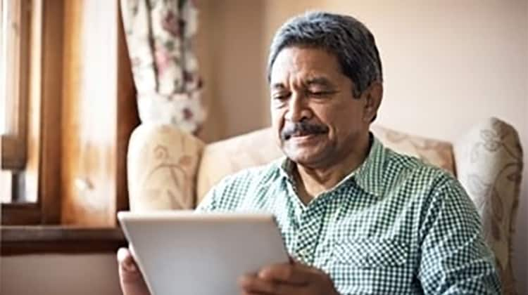 Man at home using Synzi app on his tablet