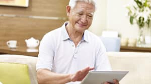 senior asian man using Synzi platform on a tablet computer