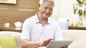 senior asian man using Synzi platform on a tablet computer