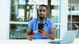 male doctor or nurse wearing blue scrubs uniform and stethoscope sitting at desk with laptop in hospital checking mobile phone