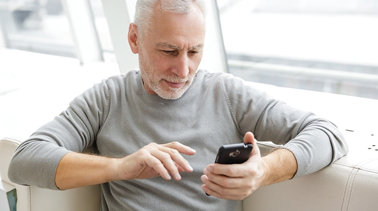 focused mature man typing on cellphone while sitting