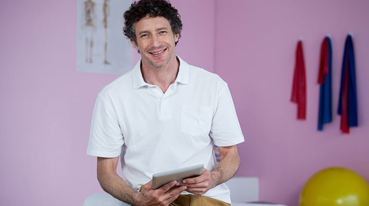 Portrait of physiotherapist using digital tablet