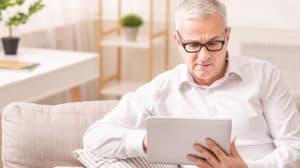 Senior man using digital tablet sitting on sofa