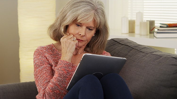 Beautiful mature woman tablet reading