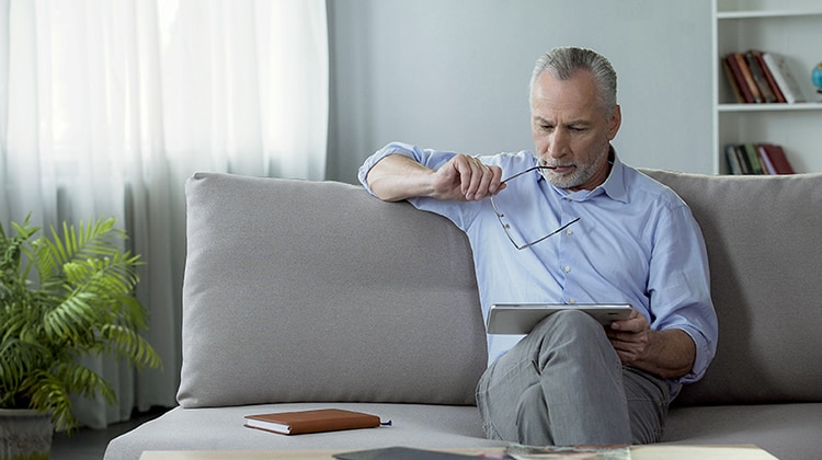 Adult male sitting on sofa and reading news on tablet, modern technologies, stock footage