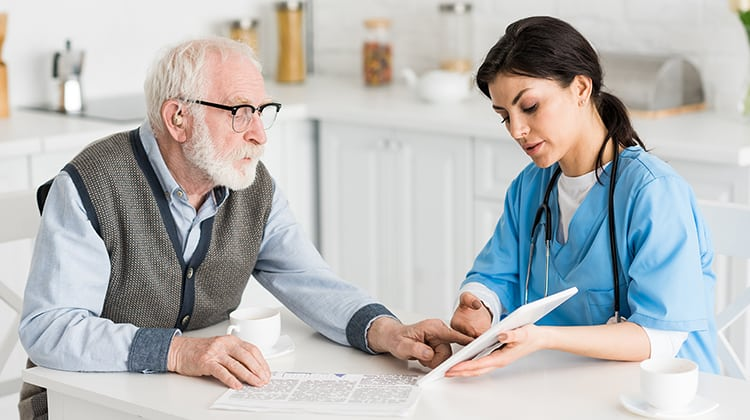 Grey haired man talking to nurse on kitchen, and using digital tablet