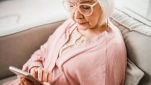 Close up of senior lady checking messages on cellphone stock photo