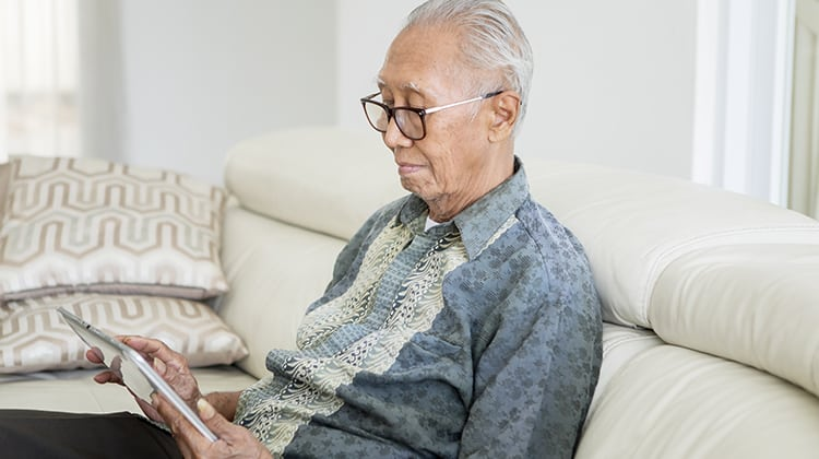 Happy senior man using a digital tablet computer while sitting on the sofa in the living room at home