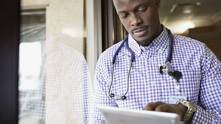 Male doctor using digital tablet in clinic