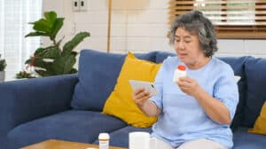Senior asian woman holding bottle of pill make video conference