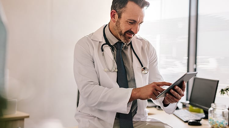 Doctor using digital tablet at his clinic