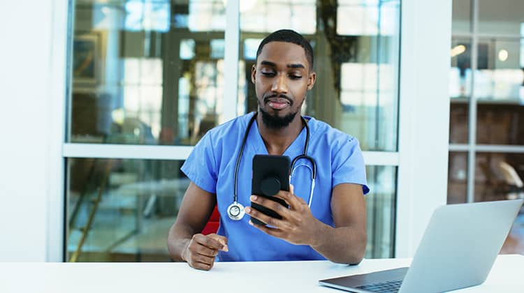 Portrait of a concerned male doctor or nurse wearing blue scrubs uniform and stethoscope sitting at desk with laptop in hospital checking mobile phone