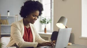 Young afro american businesswoman working on laptop with electronic documents.