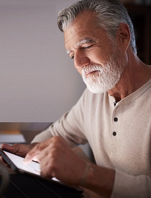 Senior Hispanic man sitting at a table using a tablet computer in the evening, close up, vertical