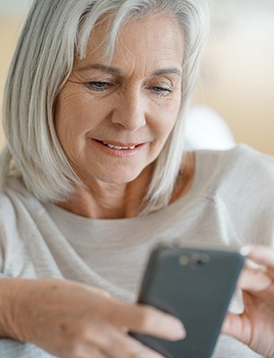 Senior woman in sofa using smartphone