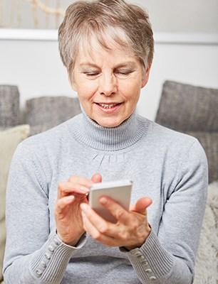 Alte Frau schreibt SMS oder installiert App auf dem Smartphone